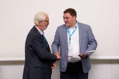 Der Präsident des Bundesverbandes Geothermie Dr. Erwin Knapek überreicht Klas Lüders (CAU) den Preis als bester Nachwuchswissenschaftler.